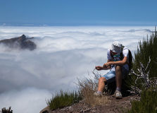 The tourist sits on break over clouds Royalty Free Stock Photo