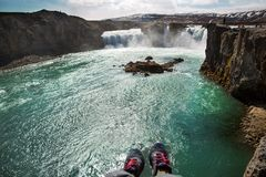 Tourist sits on a cliff near the river, hanging his legs down, v stock photography