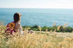 Tourist sits on coast and looks into the distance Stock Images
