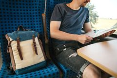 A tourist sits by the window in a train or commuter train and looks at a map.  stock images