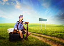 Tourist sittind on the luggage in the countryside near the dirty Royalty Free Stock Images