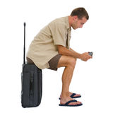 Tourist sitting on bag and checking photos Royalty Free Stock Photography