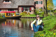 Tourist sitting by the canal Stock Images
