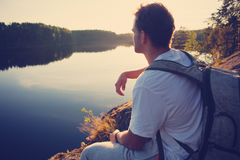 Tourist sitting on the cliff above the lake and looking far away at sunset Royalty Free Stock Images
