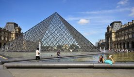 Tourist Sitting In Front Of Pyramid Of Louvre Museum In Paris France Royalty Free Stock Photos