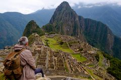 Tourist sitting on his back watching Machu Picchu Lost City of Inca. Peru. One of the New Seven Wonders of the World Royalty Free Stock Photos