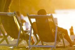 Tourist sitting in long chair on the beach of Taganga, Colombia Royalty Free Stock Photos