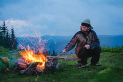 Tourist sitting near camping fire at twilight in the mountain Royalty Free Stock Photography