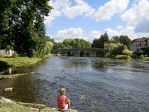 Tourist sitting near river in Bourdeilles, Dordogne, France Royalty Free Stock Images