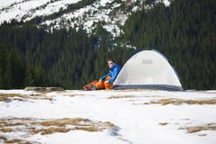 Tourist sitting near a tent and a backpack. Royalty Free Stock Images