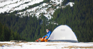 Tourist sitting near a tent and a backpack. Stock Photography