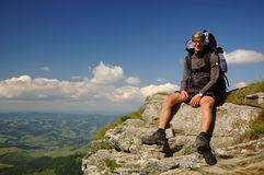 The tourist sitting on the rock. Stock Images