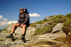 The tourist sitting on the rock. Stock Image