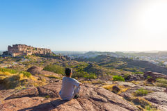 Tourist sitting on rock and looking at expansive view of Jodhpur fort from above, perched on top dominating the blue town. Travel. Destination in Rajasthan royalty free stock photo