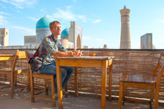 Tourist sitting in a roof-teahouse in the old city of Bukhara Stock Photo