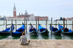 Tourist sitting in San Marco Square in Venice, enjoying the view of Gondolas in Grand Canal and San Giorgio Maggiore Church in the Stock Images