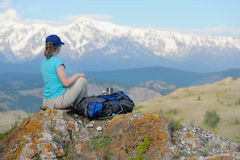 Tourist sitting on top of a cliff looking over the mountains. Stock Photo