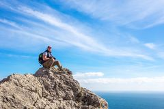 Tourist sitting on top of the mountain looking into the distance royalty free stock images