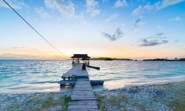 Tourist sitting on wooden jetty at sunrise, Indonesia Royalty Free Stock Image