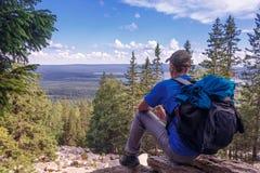 Tourist sitzen auf eine Bergoberseite Lizenzfreie Stockfotos