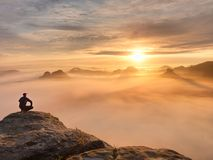 Tourist sitzen auf Spitze des Sandsteinfelsens und -c$aufpassens in bunten Nebel und in Nebel im Morgental Trauriger Mann Stockfotos
