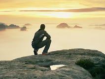 Tourist sitzen auf Spitze des Sandsteinfelsens und -c$aufpassens in bunten Nebel und in Nebel im Morgental Trauriger Mann Lizenzfreie Stockfotos
