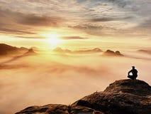 Tourist sitzen auf Spitze des Sandsteinfelsens und -c$aufpassens in bunten Nebel und in Nebel im Morgental Trauriger Mann Lizenzfreies Stockfoto