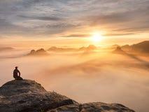 Tourist sitzen auf Spitze des Sandsteinfelsens und -c$aufpassens in bunten Nebel und in Nebel im Morgental Trauriger Mann Stockfotografie