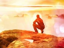 Tourist sitzen auf Spitze des Sandsteinfelsens und -c$aufpassens in bunten Nebel und in Nebel im Morgental Trauriger Mann Mann si Stockbilder