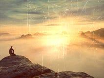 Tourist sitzen auf Spitze des Sandsteinfelsens und -c$aufpassens in bunten Nebel und in Nebel im Morgental Trauriger Mann Mann si Lizenzfreie Stockbilder