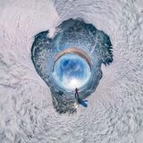 Tourist with sleds walks along the blue ice of Lake Baikal. Spherical 360 panorama little planet.  Stock Images