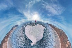Tourist with sleds walks along the blue ice of Lake Baikal. Wide-angle panorama.  Royalty Free Stock Photo