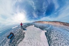Tourist with sleds walks along the blue ice of Lake Baikal. Wide-angle panorama.  Stock Image
