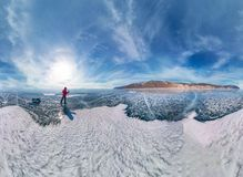 Tourist with sleds walks along the blue ice of Lake Baikal. Wide-angle panorama.  Royalty Free Stock Image