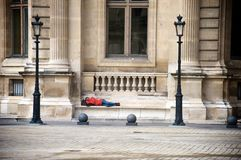 Tourist sleeping on a bench outside the Louvre Museum in Paris Royalty Free Stock Photo