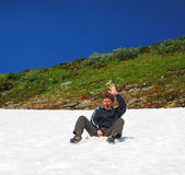 Tourist sliding on the snowfield in summer. Stock Photos