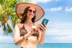 Tourist with smart phone on beach needs data roaming Stock Photo