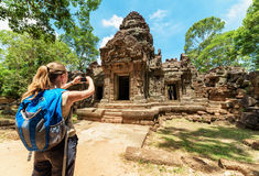 Tourist with smartphone among the ruins of Angkor, Cambodia Royalty Free Stock Photos