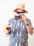 Tourist Snapping a Picture. A senior tourist man in Hawaiian shirt, takes a picture with his camera while holding a fruity tropical drink in the other hand Royalty Free Stock Photography