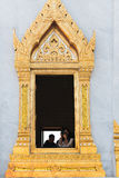 Tourist snaps a photo from an ornate window of Wat Traimit, an i Stock Photo