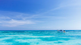 A tourist speed boat in crystal clear blue sea at tropical islan Royalty Free Stock Image
