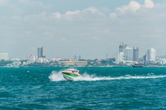 Tourist speed boat running on sea in Pattaya bay. With background of Pattaya city in a mist royalty free stock photography