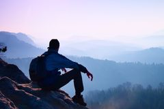 Tourist with sporty backpack sit on rocky peak  and watching into misty valley bellow. Sunny misty daybreak in rocky mountains. Royalty Free Stock Photos