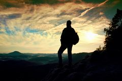 Tourist with sporty backpack stand on rocky view point and watching into deep misty valley bellow. Sunny spring daybreak in rocky. Mountains stock photo