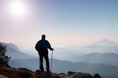 Tourist with sporty backpack stand on rocky view point and watching into misty valley bellow. Sunny misty daybreak in rocky mounta Royalty Free Stock Photography
