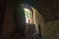 Tourist standing in arch of weathered dark corridor of old fortr. Ess Royalty Free Stock Images