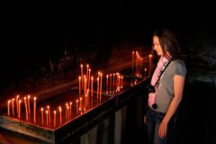 Tourist standing by the candles in Ostrog Monastery, Montenegro Stock Images