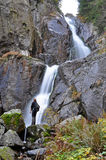 Tourist standing in the front of a waterfall Royalty Free Stock Images