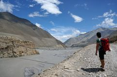 The tourist is standing and looking at the suspension bridge across the Kali Gandaki River. MUSTANG/ NEPAL -August 21: The tourist is standing and looking at Royalty Free Stock Images