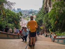 Tourist Standing in the middle of Stairs in Batu Caves, Malaysia. Seems he waiting for his friend or afraid to walking down from the Batu Caves Temple Stock Photo